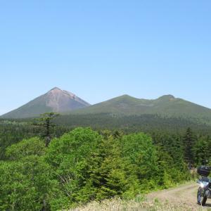 一直線な林道と阿寒の山並み