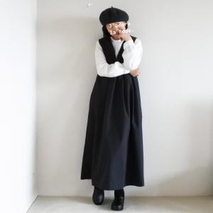 黒いジャンバースカートと、ハイネックの白いブラウス。
