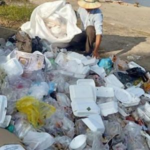 ゴミの山にたたずむ、痩せ形クメール女性のポートレイト写真です。