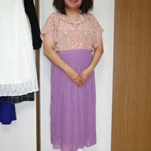 ピンクベージュのセーラー襟ブラウスにラベンダー色のマキシ丈プリーツスカート