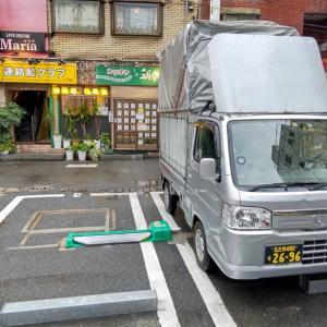 小倉駅近くの駐車場に軽トラックを停め、知り合いの
