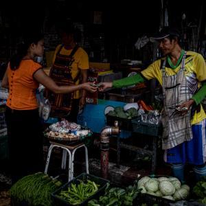 男は八百屋で女性客にお釣りを渡していた (タイ)