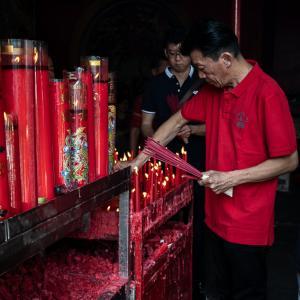 赤いロウソクを片付ける赤いポロシャツの男 (インドネシア)