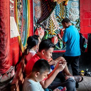 鳳凰の前で携帯ゲームに興ずる男の子 (インドネシア)