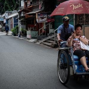 大きな日傘と一緒に走るベチャ (インドネシア)