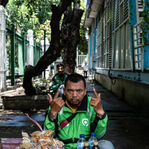 街路樹の下で休んでいたGOJEKの運転手 (インドネシア)