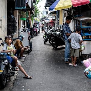 ベンチ代わりにバイクに腰掛ける男の子 (インドネシア)