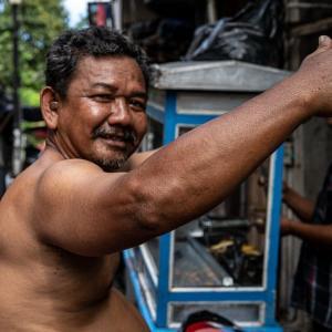 腕を上に挙げた上半身裸の男 (インドネシア)