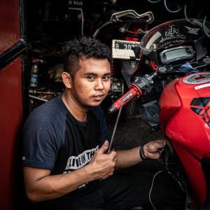 赤いバイクを整備していた青年 (インドネシア)