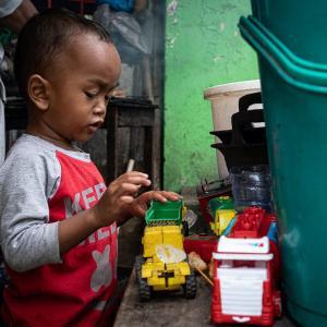 働くクルマで遊ぶ幼い男の子 (インドネシア)
