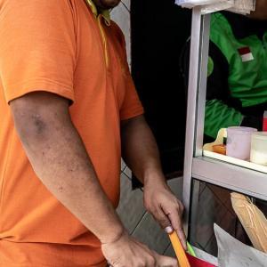 すり鉢でスパイスを潰す男 (インドネシア)