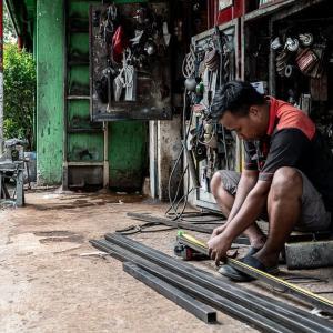 巻き尺で鋼材の長さを測る男 (インドネシア)