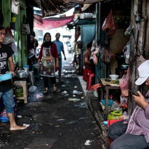 ゴチャゴチャしていた路地でくつろいでいた男 (インドネシア)
