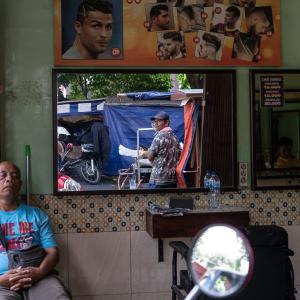 床屋の鏡の中で振り返る男 (インドネシア)