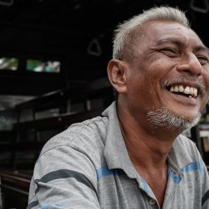 大笑いする白髪交じりの男 (インドネシア)