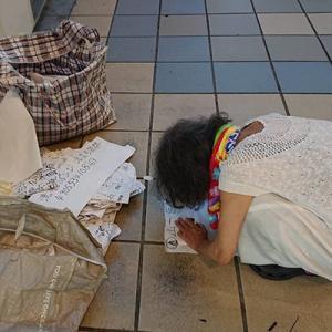京橋の京阪とJRの間の広場で紙に書いた字を掲げる謎のお婆ちゃん