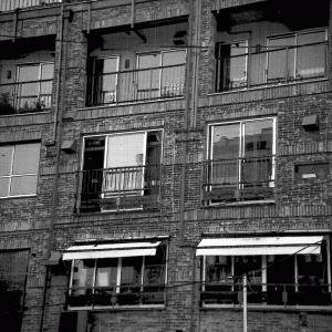どこかレトロで味わいのある総レンガ作りのビルのドアップの写真素材と、線画・トーン仕上げの漫画作成用素材です。