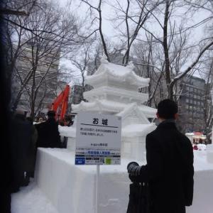 立派なお城の市民雪像の前で傘を配る青年たち