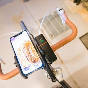 自転車にアルミ製スマホホルダーを取り付け、モバイルバッテリー機能付きライトから充電もできるように