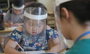 Japanese students go back to school, with face shields | AFP