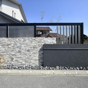 アルミフレームと石積みのある外構デザイン。