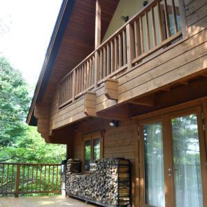 軽井沢の別荘のウッドデッキの上の薪棚に薪の配達