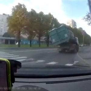 [動画0:21] トラックがカーブで横転、ゴミを撒き散らす