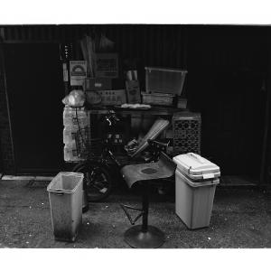 A chair and trash cans in front of a bar in the back alley in Ginza,Tokyo,Japan