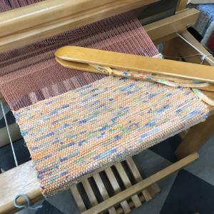 高機にかけたオレンジのたて糸はようやく織りはじめまで至りました。裂く前の布はこんな柄ですよ!!