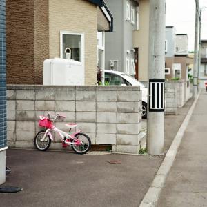 女児の自転車と高齢者の手つなぎ