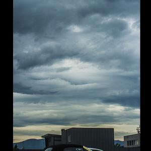 墨を流した様な雲と外車