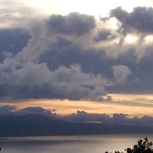 深く厚い灰色の雲と朝焼けのあいだに。