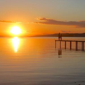 美しい夕日の湖畔に寄り添う二人、トラジメーノ湖