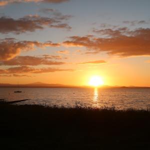 桃色の夕焼け白い月トラジメーノ湖