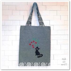 黒猫さんが木の実を見つめる…シックなブックトートバッグ。レトロ大人デザイン