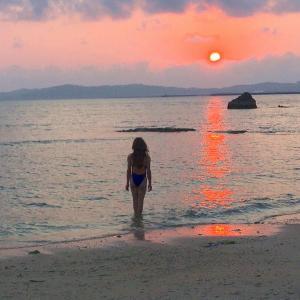 夕日とビーチと競泳水着