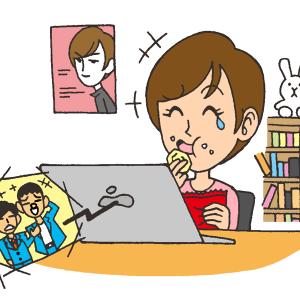 自宅でお菓子を食べながら漫才の動画を見て笑う女性