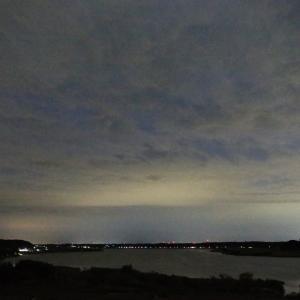 曇天の空を地上の灯が染め、いつまでも暗い沼
