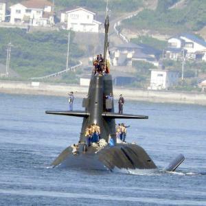潜水艦がタグボート(曳船)に曳かれ潜水艦基地に入港中。