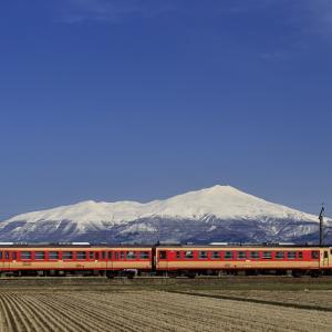 冠雪の鳥海山と急行色のキハ40