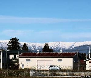 集落の空に飯豊連峰の雪が輝いて