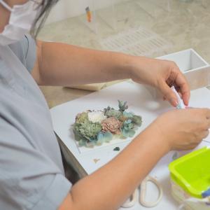 くすみ系のグリーン&ブルーのアーティフィシャルフラワーを詰め込んだフォトフレームアレンジを作成い