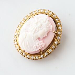 ピンクシェルカメオを芥子パールで取り巻いたブローチ。