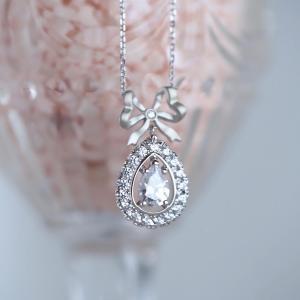 リボンがかわいいペアシェイプカットのダイヤ取り巻きネックレス。