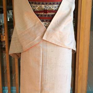 ピンクベージュ地細縞文紬と生成縞地葡萄花唐草文なごや帯