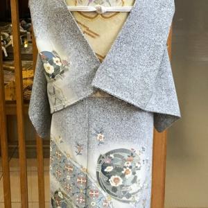 灰地熨斗花唐草文スワトー刺繍訪問着とクリーム地装飾花亀甲文綴れ袋帯