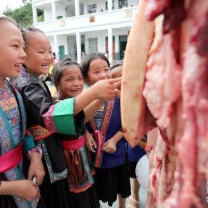 生豚肉のかたまりと生きた魚、小学生に配られる【中国】