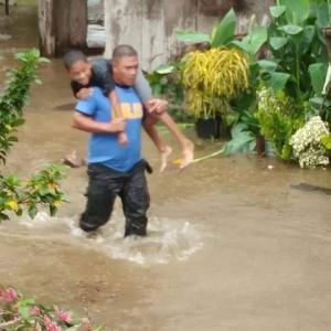 洪水で避難する子ども達を助ける警察官