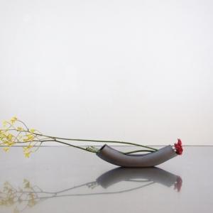 弓形の花器に曲線の茎をみせる―A/光峰窯