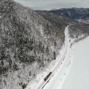 雪に閉ざされた天塩川沿いを南下する宗谷ラッセル